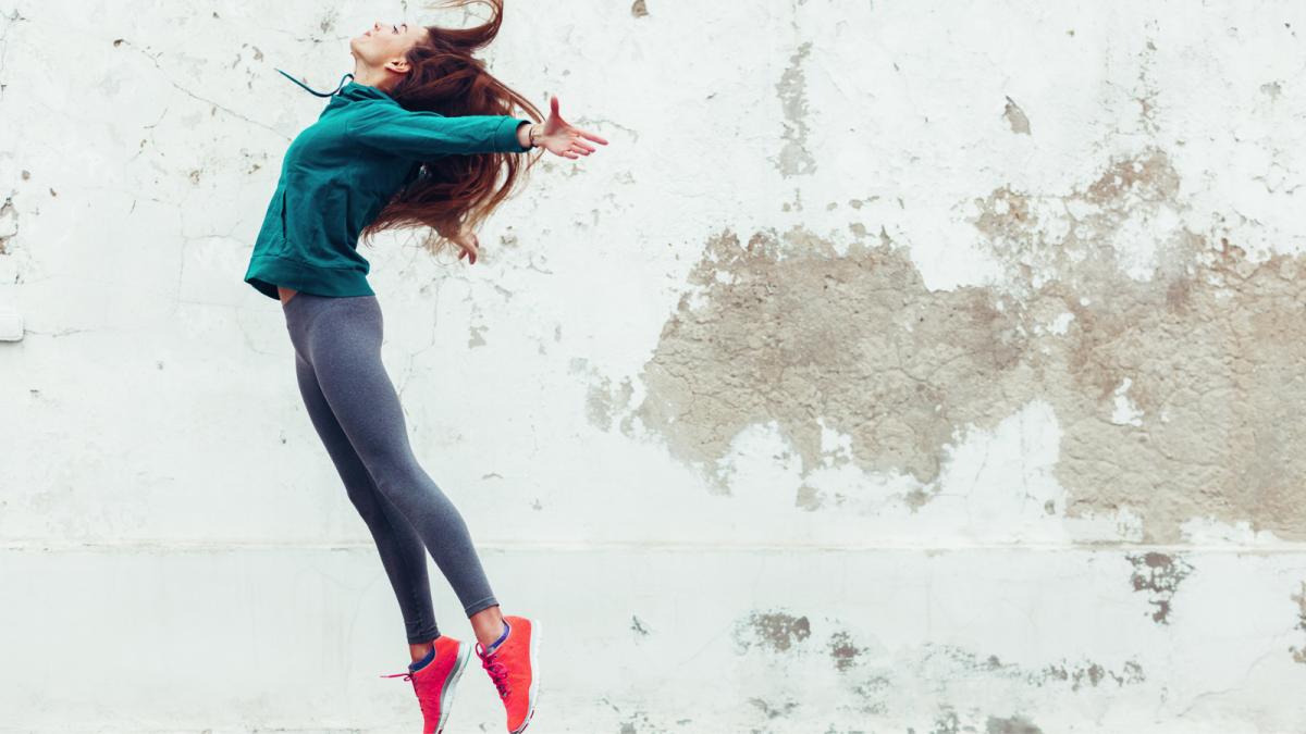 Eine junge Läuferin springt hoch